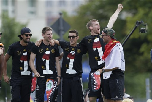 Sami Khedira, goalkeeper Ron-Robert Zieler, Mesut Ozil, Per Mertesacker and Lukas Podolski, from left, celebrate on the stage after the arrival of the German national soccer team in Berlin Tuesday, July 15, 2014. Germany beat Argentina 1-0 on Sunday to win its fourth World Cup title.  (AP Photo/Petr David Josek)
